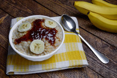 Oatmeal in a beautiful white bowl on a warm wooden background with slices of bananas  and jam. Oatmeal in a beautiful white bowl on a warm wooden background with Stock Photos