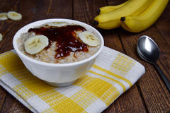 Oatmeal in a beautiful white bowl on a warm wooden background with slices of bananas  and jam. Oatmeal in a beautiful white bowl on a warm wooden background with Royalty Free Stock Photography