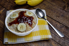 Oatmeal in a beautiful white bowl on a warm wooden background with slices of bananas  and jam. Oatmeal in a beautiful white bowl on a warm wooden background with Stock Images