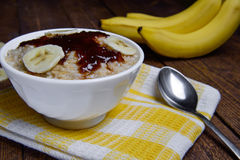 Oatmeal in a beautiful white bowl on a warm wooden background with slices of bananas  and jam. Oatmeal in a beautiful white bowl on a warm wooden background with Royalty Free Stock Photos