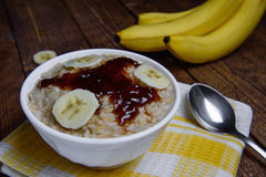 Oatmeal in a beautiful white bowl on a warm wooden background with slices of bananas  and jam. Oatmeal in a beautiful white bowl on a warm wooden background with Royalty Free Stock Photo