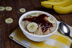 Oatmeal in a beautiful white bowl on a warm wooden background with slices of bananas  and jam Stock Photography