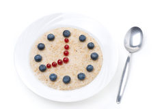 Oatmeal with berries in the form of dial and spoon, isolated Royalty Free Stock Photography