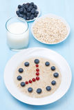 Oatmeal with berries in the form of dial, vertical Royalty Free Stock Photos