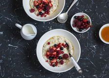 Oatmeal with berries and honey on a dark background. Stock Photos
