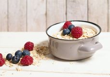 Oatmeal and berries. Oatmeal in grey pot and fresh raspberries and blueberries on white wooden table Stock Images