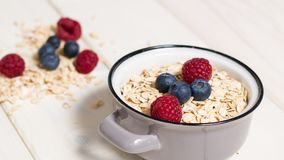 Oatmeal and berries. Small pot of rolled oats with some berry fruit on top. Wide screen,selective focus royalty free stock photos