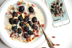 Oatmeal with blackberries and goji seeds and telephone Stock Photo