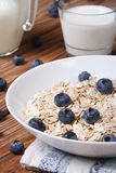 Oatmeal with blueberries and milk close-up vertical Royalty Free Stock Images