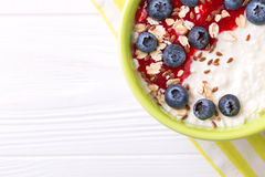 Oatmeal with blueberries, raspberry jam, flax seeds and yogurt. At rustic wooden table. Breakfast smoothie bowl. Flat lay, top view Stock Photos