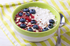Oatmeal with blueberries, raspberry jam, flax seeds and yogurt. At rustic wooden table. Breakfast smoothie bowl. Horizontal view Stock Photography