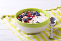 Oatmeal with blueberries, raspberry jam, flax seeds and yogurt. At rustic wooden table. Breakfast smoothie bowl. Horizontal view Royalty Free Stock Photography