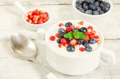 Oatmeal with blueberries and strawberries in the white bowl Royalty Free Stock Photos