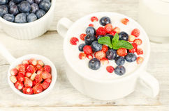 Oatmeal with blueberries and strawberries in the white bowl Royalty Free Stock Photo