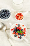 Oatmeal with blueberries and strawberries in the white bowl Royalty Free Stock Images