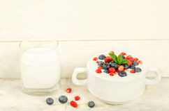 Oatmeal with blueberries and strawberries in the white bowl Royalty Free Stock Image