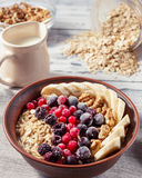 Oatmeal in bowl with berries, bananas and walnuts Stock Photography