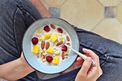 Oatmeal bowl with berries. Girl eating breakfast royalty free stock photo