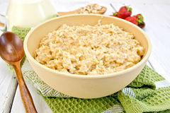 Oatmeal in bowl on light board Royalty Free Stock Photos