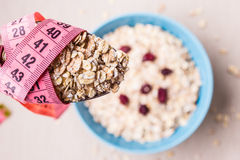 Oatmeal in bowl and measuring tape around spoon Royalty Free Stock Image