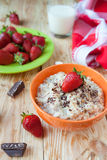 Oatmeal in a bowl with milk and strawberries, Royalty Free Stock Image