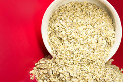 Oatmeal in a bowl. On red background Stock Photo