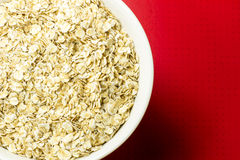 Oatmeal in a bowl. On red background Stock Images