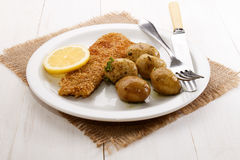 Oatmeal breaded kipper and baby potatoes with herbs Stock Image