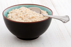 Oatmeal breakfast. Delicious nutritious and healthy fresh old fashioned oatmeal on antique wood table Stock Images