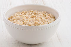 Oatmeal breakfast. Delicious nutritious and healthy fresh old fashioned oatmeal on antique wood table Stock Image