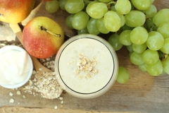 Oatmeal breakfast smoothie with grapes, pear and yogurt in top view Royalty Free Stock Photography