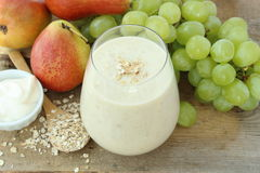 Oatmeal breakfast smoothie with grapes, pear and yogurt. On wooden board Stock Images