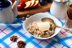 Oatmeal with butter, berries and nuts for breakfast with tea Stock Images