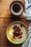 Oatmeal with butter and dates. Oatmeal with butter and figs on a wooden table Royalty Free Stock Photo