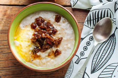 Oatmeal with butter and dates. Oatmeal with butter and figs on a wooden table Royalty Free Stock Image