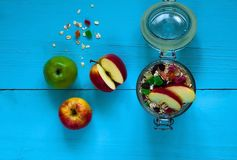 Oatmeal with candied fruits and apples, Healthy ingredients for breakfast. Homemade granola in an open glass jar, on a colored wooden background, top view Royalty Free Stock Image