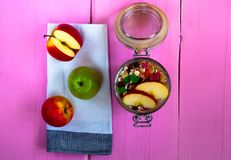 Oatmeal with candied fruits and apples, Healthy ingredients for breakfast. Granola in an open glass jar on a fabric texture on a pink background, top view Royalty Free Stock Photos