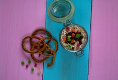 Oatmeal with candied fruits and bread straws. Healthy ingredients for breakfast. Homemade granola in an open glass jar, on a colored wooden background, top Royalty Free Stock Photos