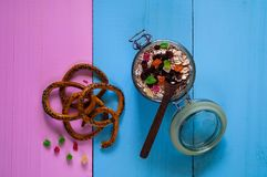 Oatmeal with candied fruits and bread straws. Healthy ingredients for breakfast. Homemade granola in an open glass jar and wooden spoon, on a colored wooden Stock Images