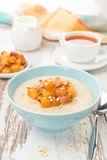 Oatmeal with caramelized peaches, tea and yogurt for breakfast Royalty Free Stock Photos