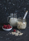 Oatmeal cereal, milk, raspberries - raw ingredients for cooking a healthy breakfast. On a dark background Royalty Free Stock Photography