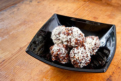 Oatmeal chocolate balls. Pile oatmeal chocolate cookies with desiccated coconut in black bowl Stock Photo
