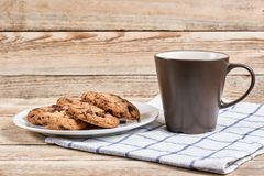 Oatmeal Chocolate Chip cookie. Oatmeal cookies with chocolate slices in white plate and brown cup on napkin on a wooden background Royalty Free Stock Photography