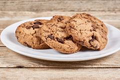 Oatmeal Chocolate Chip cookie. Oatmeal cookies with chocolate slices in a white plate on a wooden background Royalty Free Stock Images