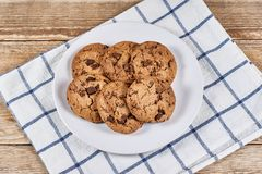 Oatmeal Chocolate Chip cookie. Oatmeal cookies with chocolate slices in white plate and napkin on a wooden background Stock Photography