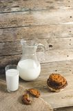 Oatmeal chocolate chip cookies, jug and glass of milk, rustic wooden background. Country dinner Royalty Free Stock Photo