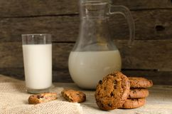 Oatmeal chocolate chip cookies, jug and glass of milk, rustic wooden background. Country dinner Stock Photos
