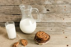 Oatmeal chocolate chip cookies, jug and glass of milk, rustic wooden background. Country dinner Stock Photography