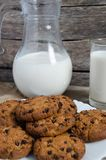 Oatmeal chocolate chip cookies, jug and glass of milk, rustic wooden background. Country dinner Stock Image