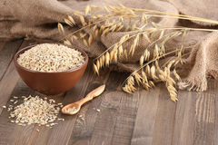 Oatmeal in a clay bowl, stalks of oats on the background of wood Stock Images